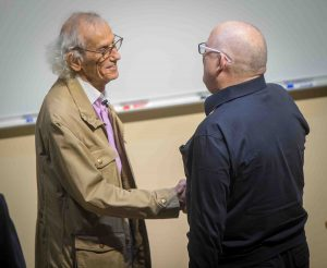 World-famous environmental artist Christo shakes the hands of Professor Ed Kerns after giving the 2018 Grossman Visiting Artist lecture.