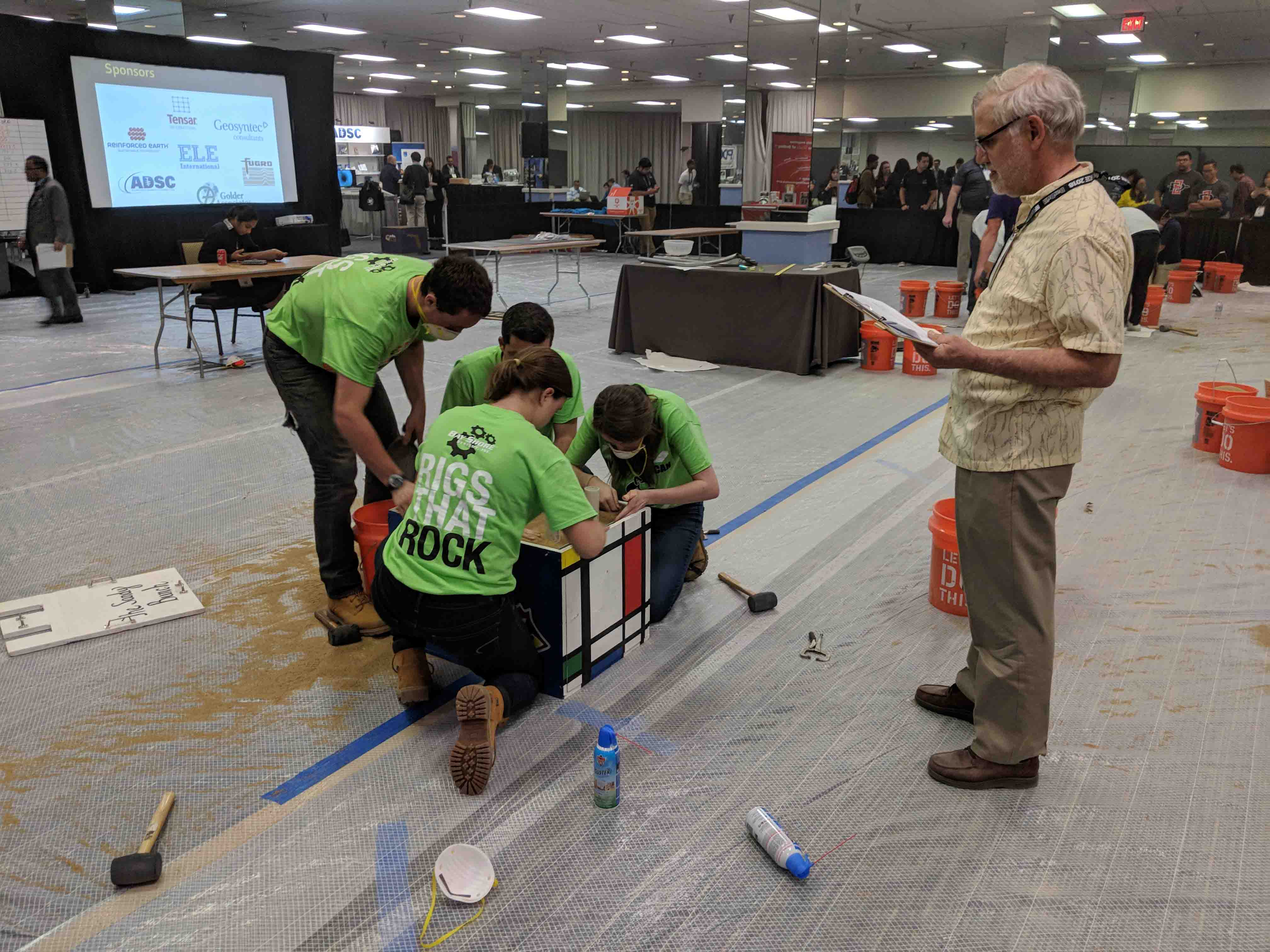 Lafayette students assemble a project in the Geotechnical Engineering Competition as a judge watches.