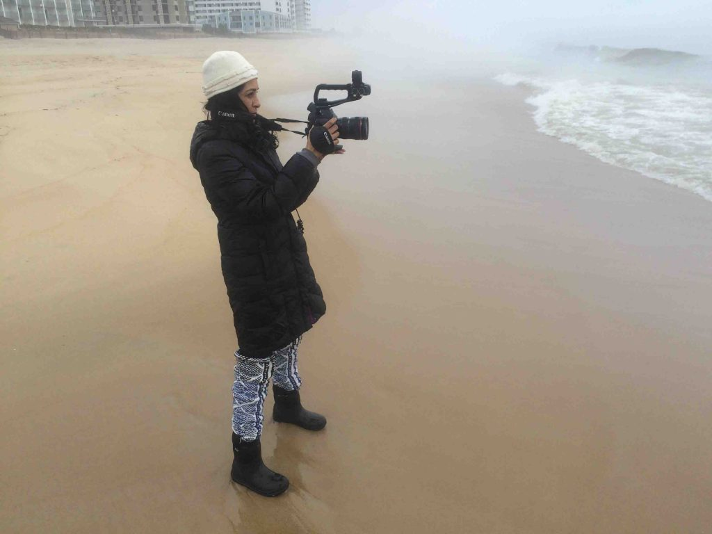 Film and media studies professor Nandini Sikand films the water on a beach.