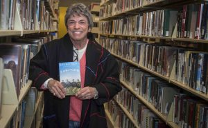 Pioneering feminist, activist, and author Rita Mae Brown holds a copy of her book Cakewalk.