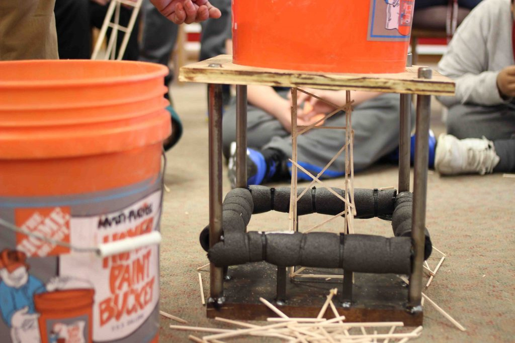 A bucket on top of a balsa wood model tower tests its strength.