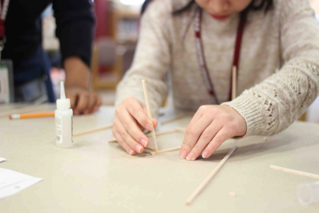A student works to create a balsa wood model tower.