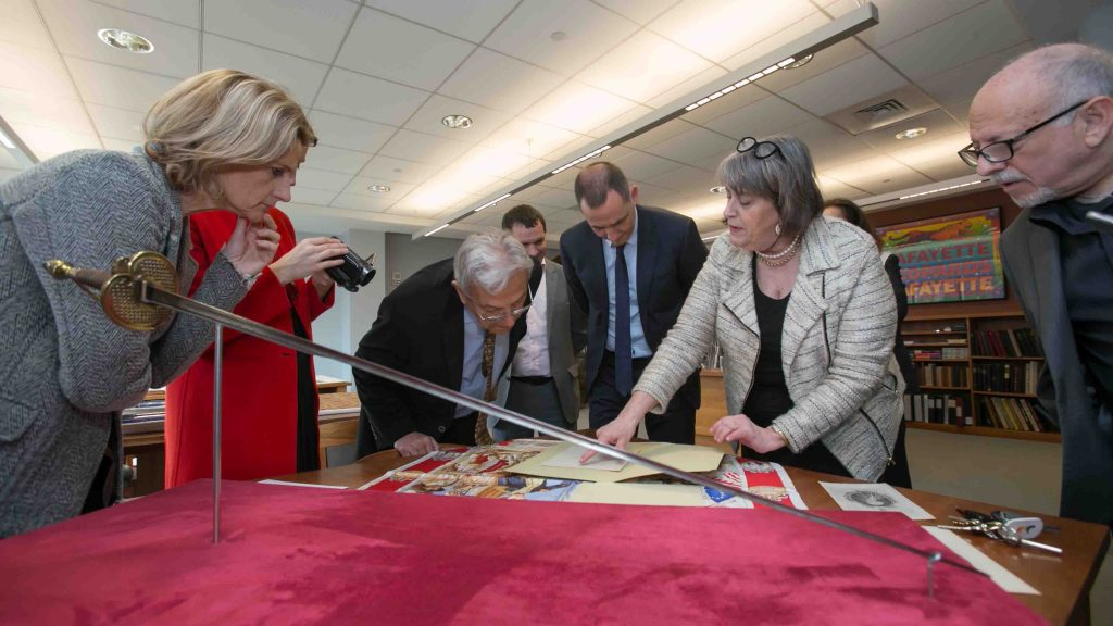 Diane Shaw, director of Special Collections, shows members of the Corsican delegation items from the College Archives.
