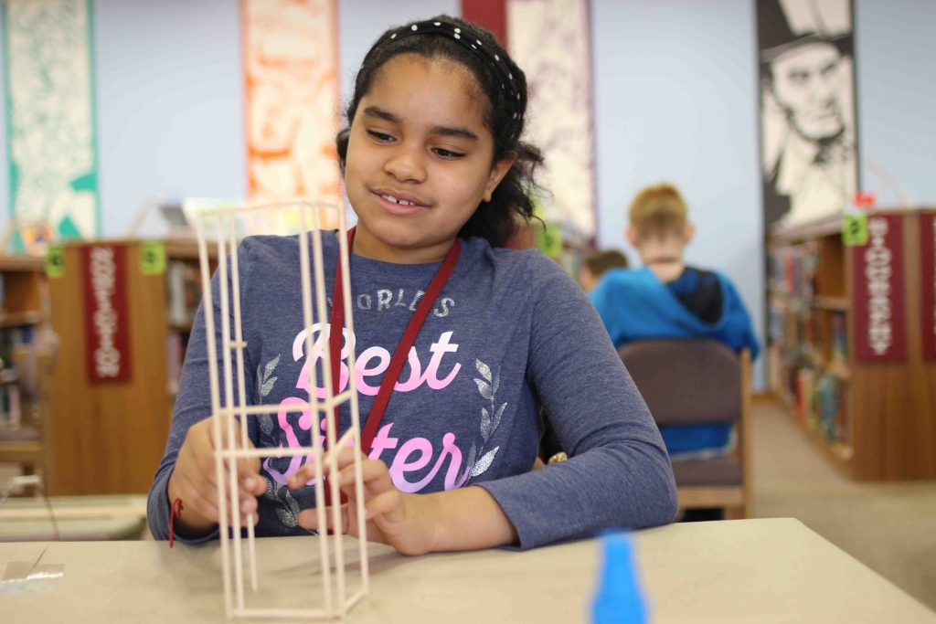 A young girl positions her balsa wood model tower.