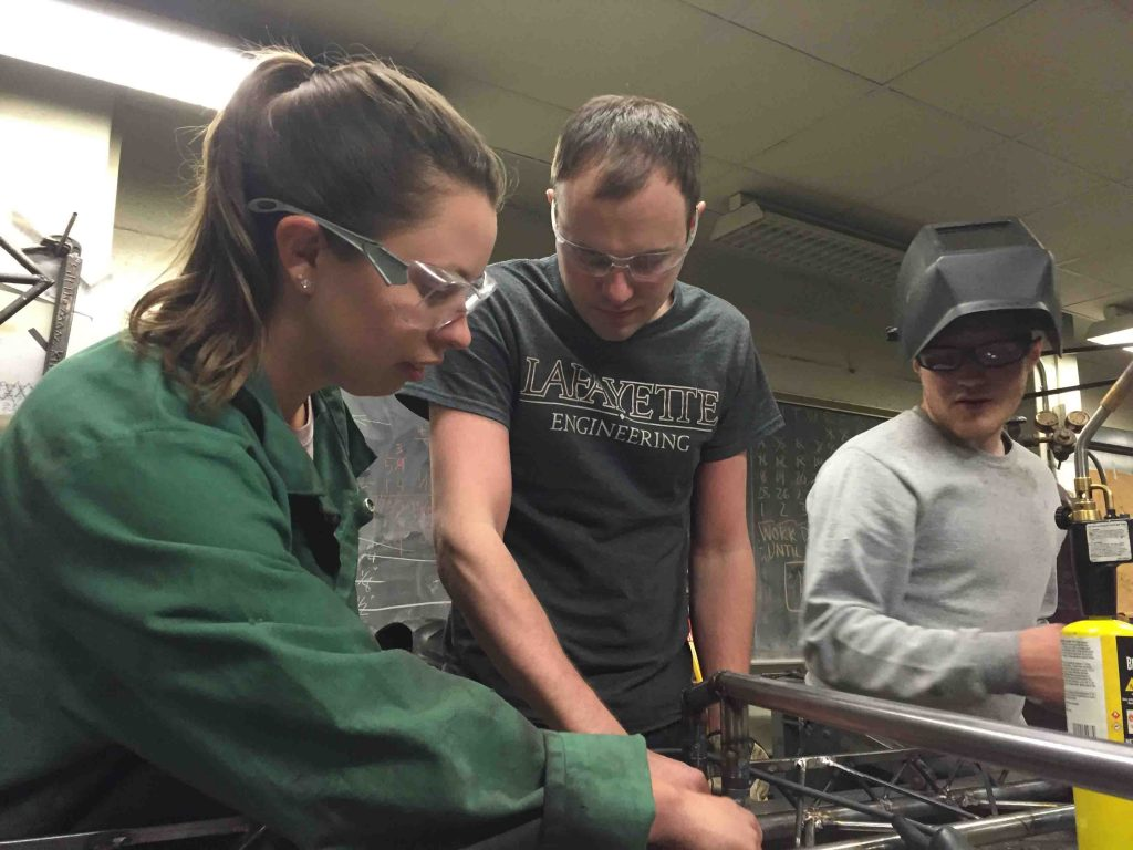 Students work on their steel bridge model.