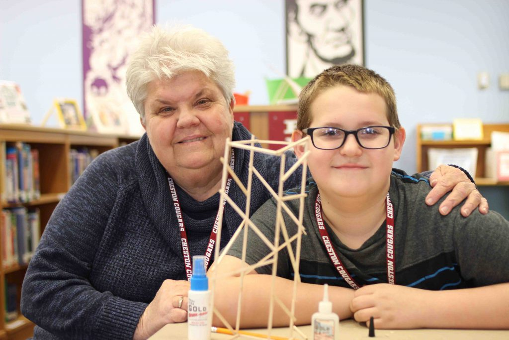 A teacher and student with his balsa wood model tower