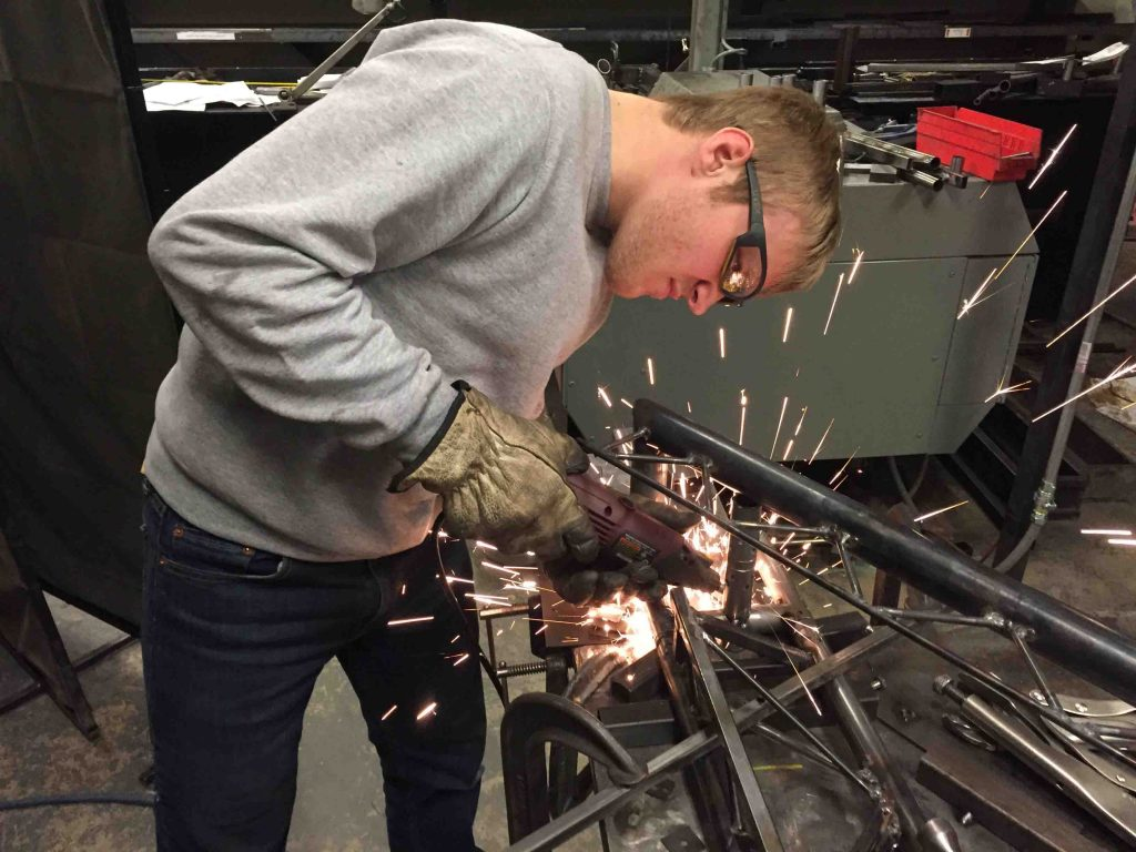 Travis Shoemaker '18 solders the steel bridge model.
