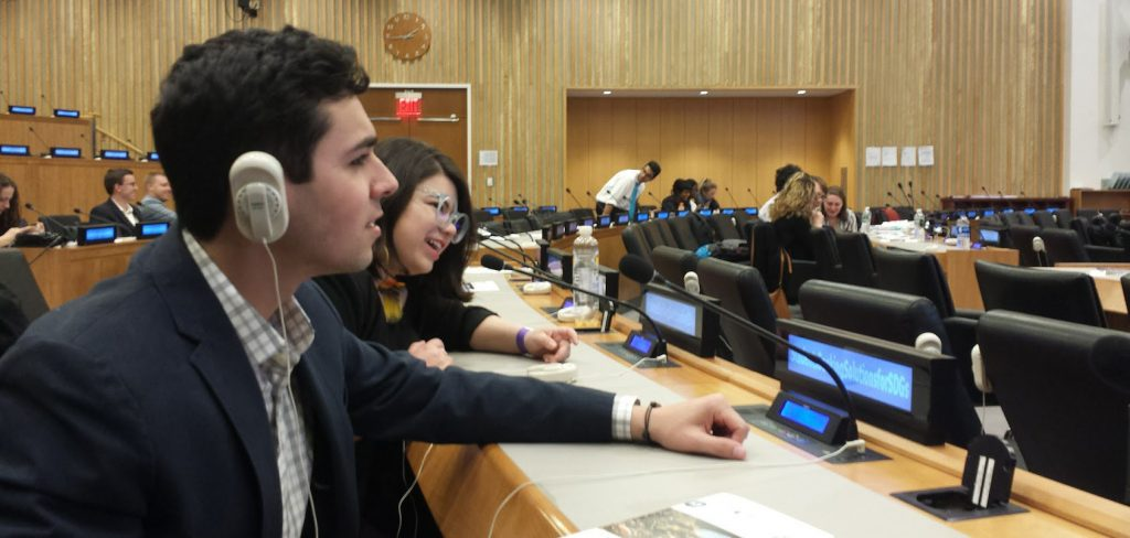 Students sit inside the United Nations assembly room.
