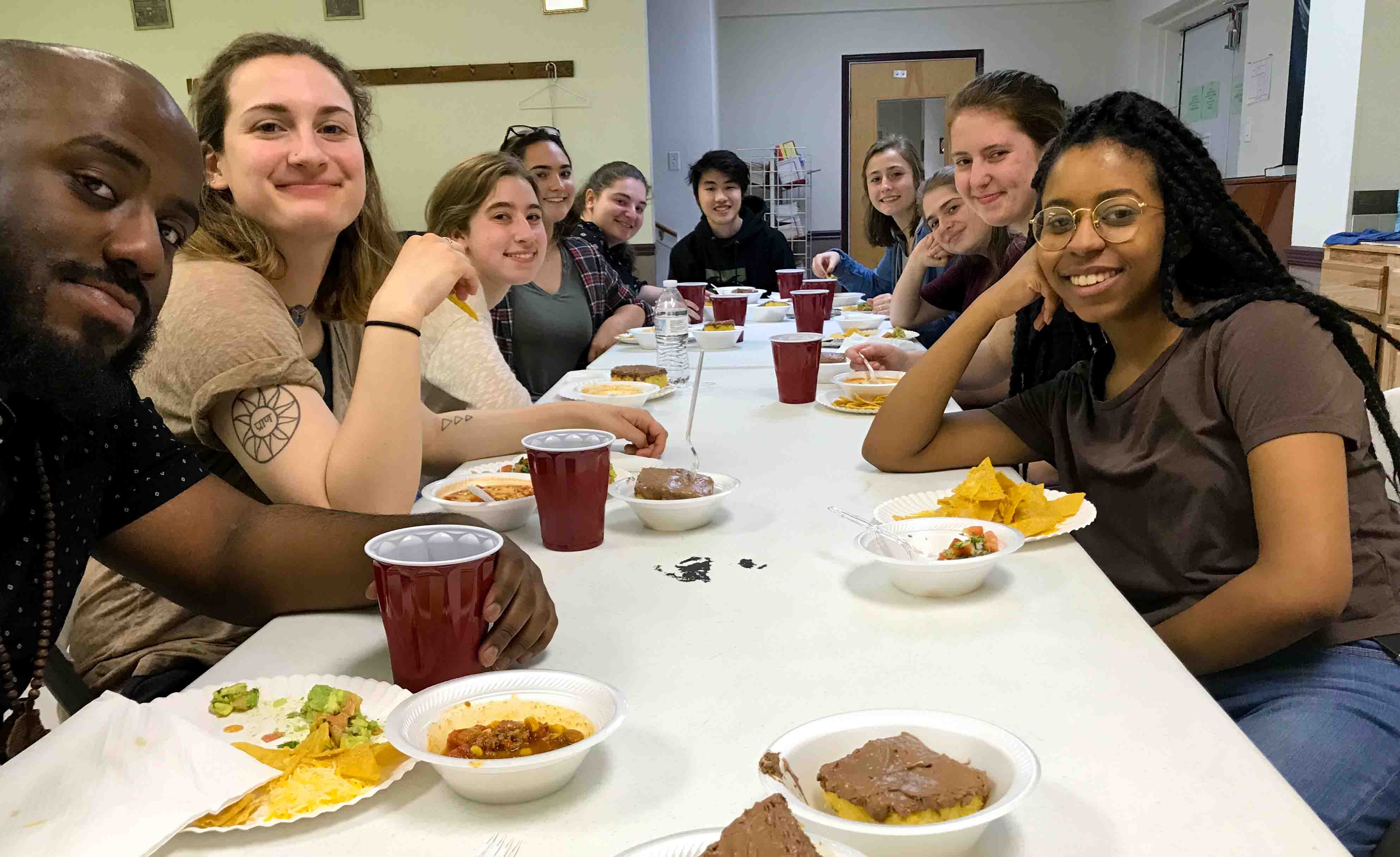 Students pose for a photo while seated for a meal during their Alternative School Break trip to serve and learn about the Texas criminal justice system.