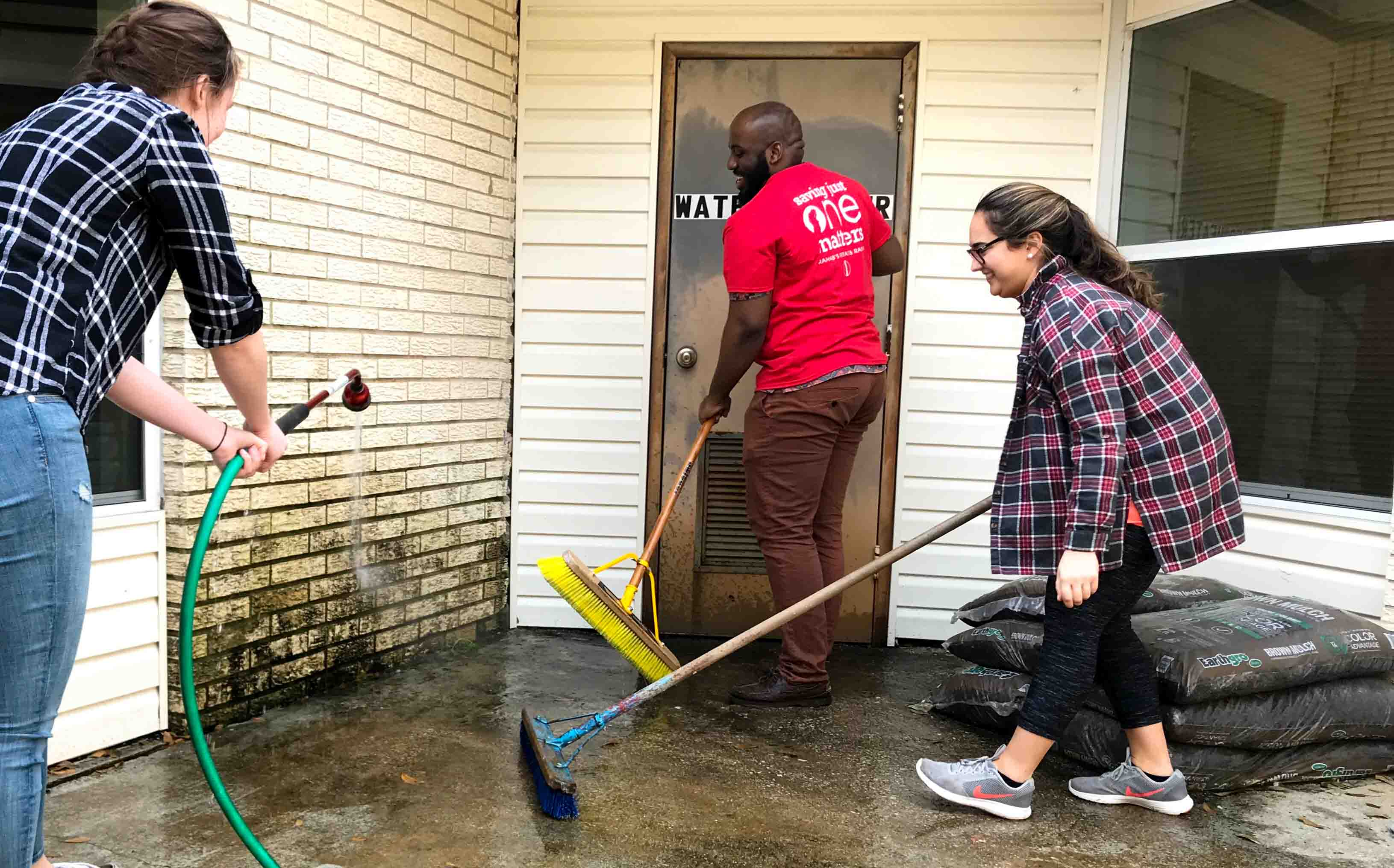 Three students use a water hose and brooms to clean during their Alternative School Break trip to serve and learn about the Texas criminal justice system.