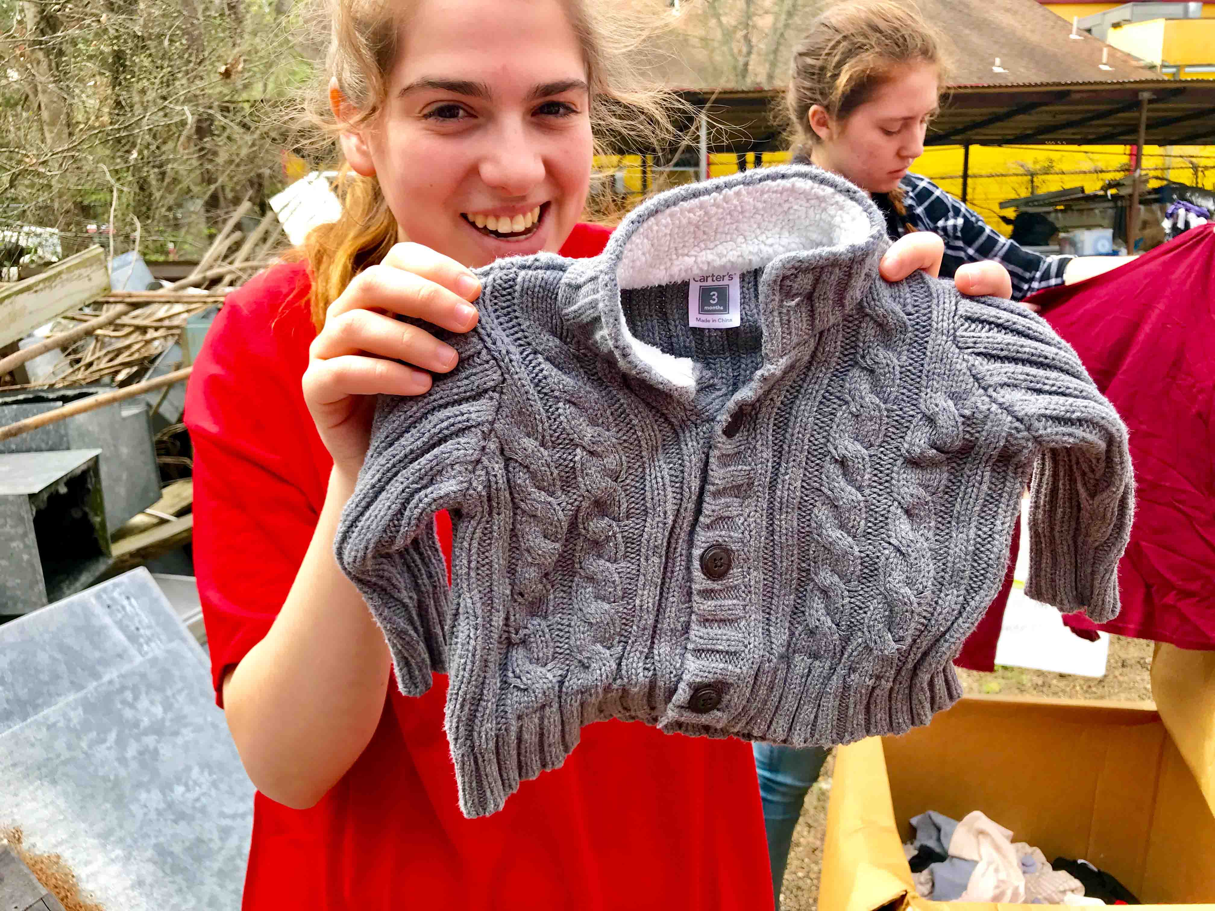 A student holds up a children's sweater during the Alternative School Break trip to serve and learn about the Texas criminal justice system.