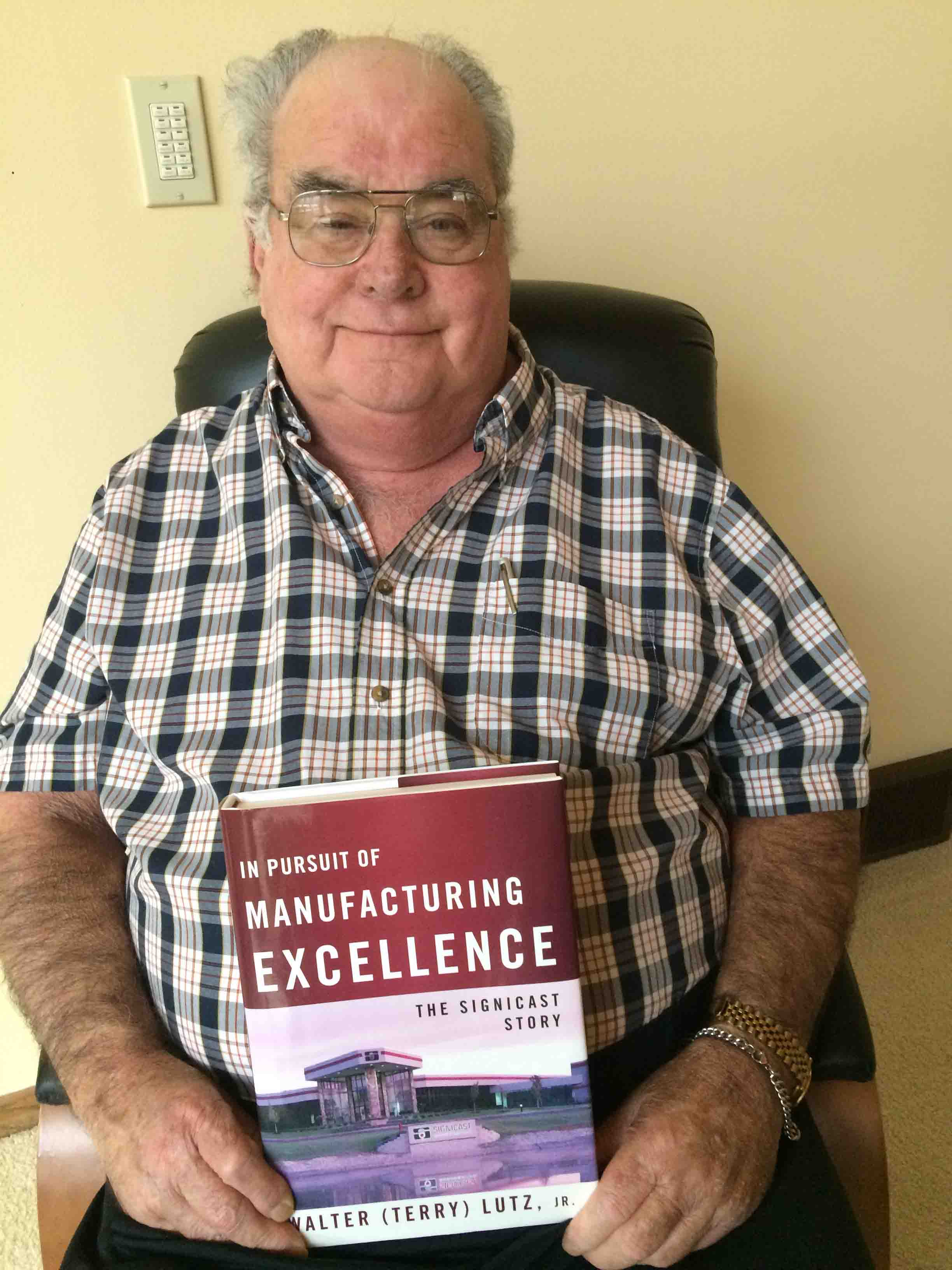Terry Lutz '62 holds a copy of his book, In Pursuit of Manufacturing Excellence – The Signicast Story.