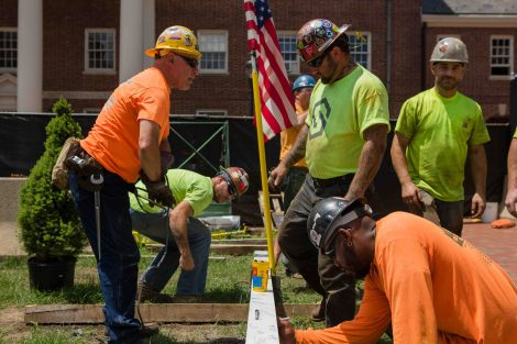 Construction workers sign an I-beam during the topping-out ceremony for Rockwell Integrated Sciences Center.