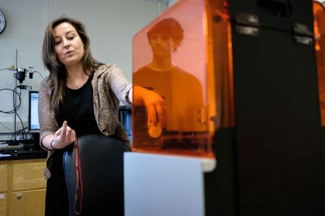 A professor grabs a product from the 3D printer.