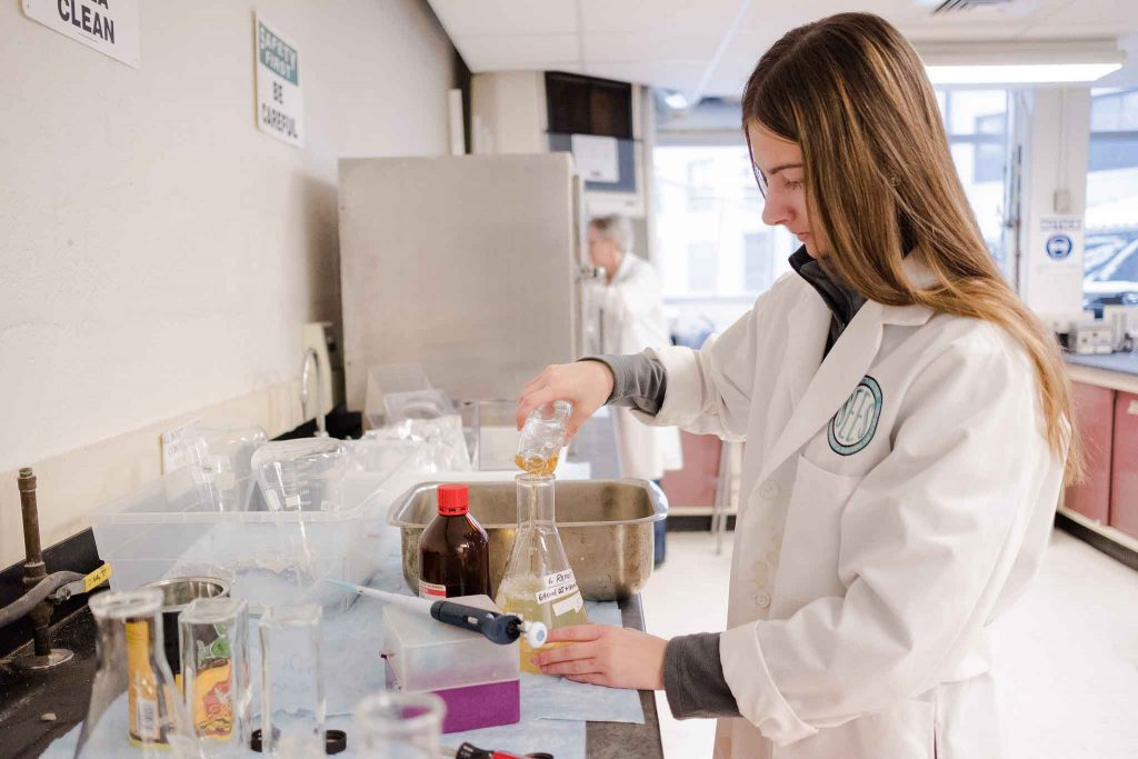 A student works in the lab on the biofilm project.
