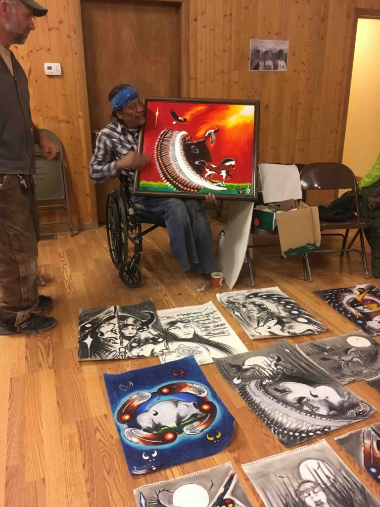 A man in a wheelchair displays his paintings on the floor as another man looks on.