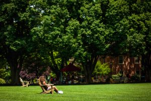 A student sits in an Adirondack chair on the Quad.