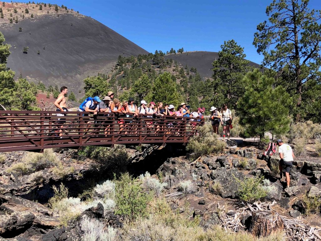 Students explore Sunset Crater National Monument, home of Sunset Crater, the cinder cone volcano in the background.
