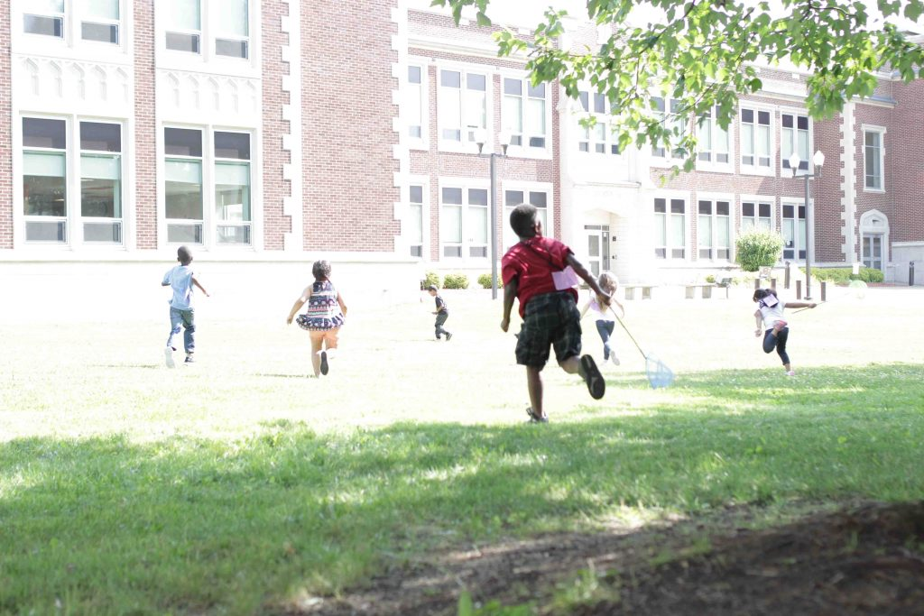 Children run on school grounds.