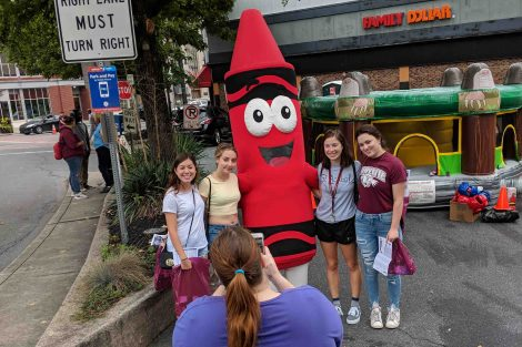 Four students pose with the Crayola crayon mascot.