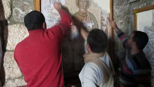 Men appear to be scratching off a Western religious painting.