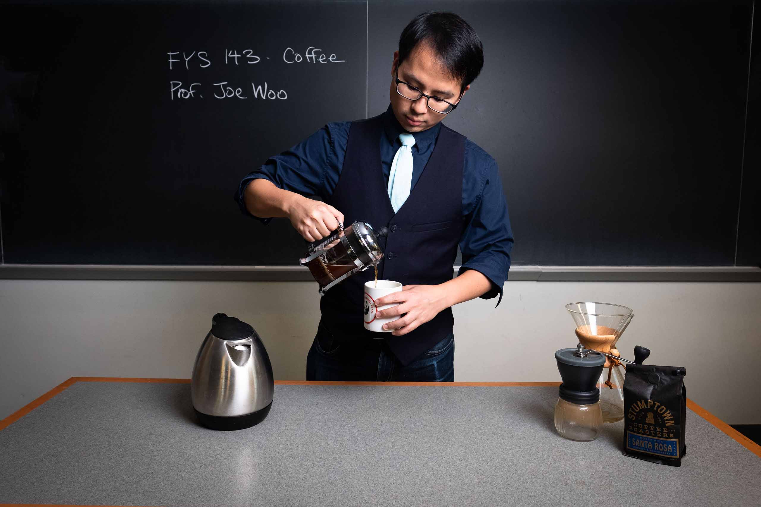 Professor Joe Woo pours a cup of coffee in his classroom.