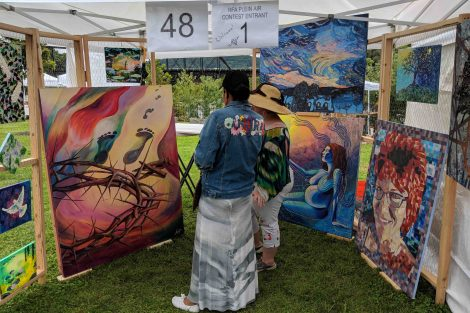 Two people look at paintings at the Riverside Festival of the Arts in Easton.