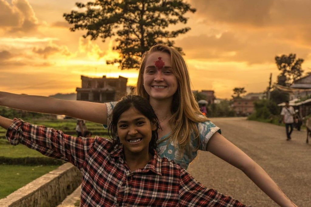 Thea Dekker and a girl smile and pose for a photo during sunset