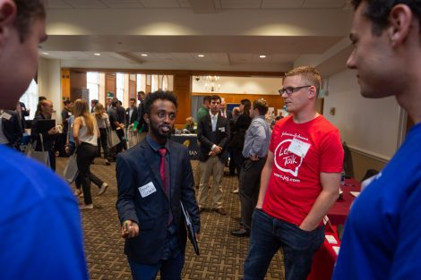 A student and professional talk at the annual fall career fair.