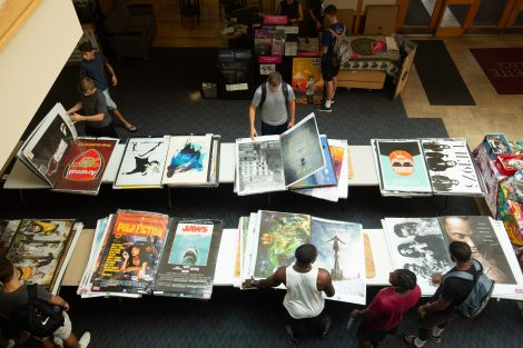 Students look at large posters in the Farinon atrium.