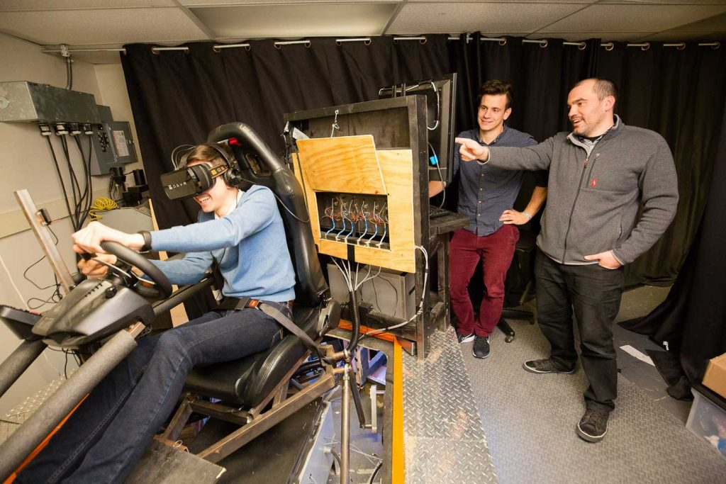 The three researchers test the autonomous vehicle simulator.