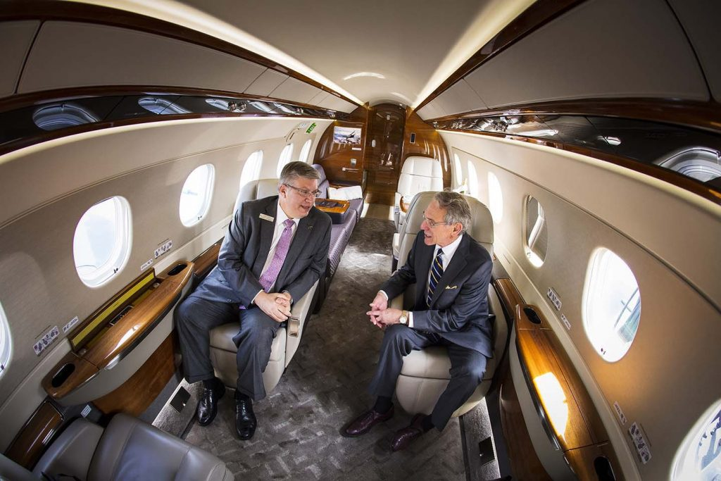 Two business travelers chat inside the plane.