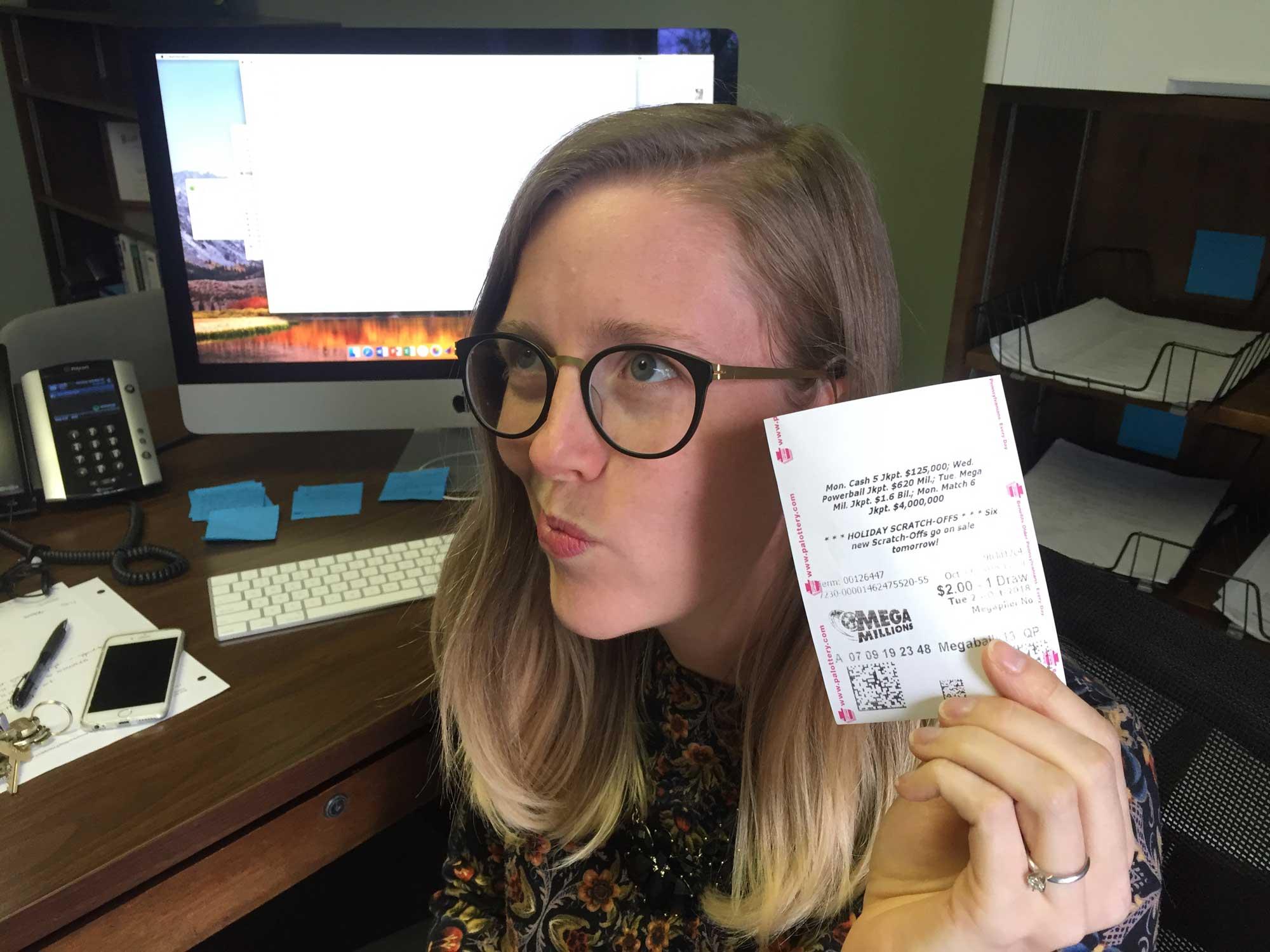 Professor Erin Cottle Hunt holds a lottery ticket.