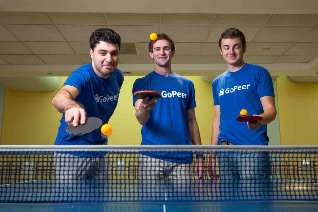 Three students wearing GoPeer T-shirts play around with pingpong balls and paddles.
