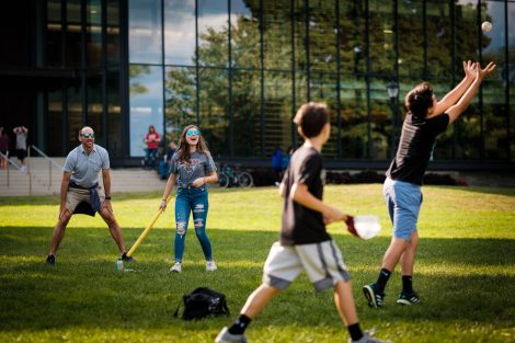 A family plays whiffleball on the Quad.