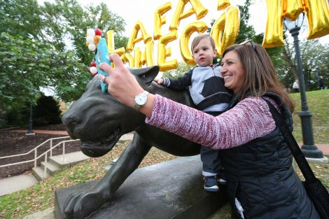 An alumna takes a photo of her and her baby by the leopard statue during Homecoming.