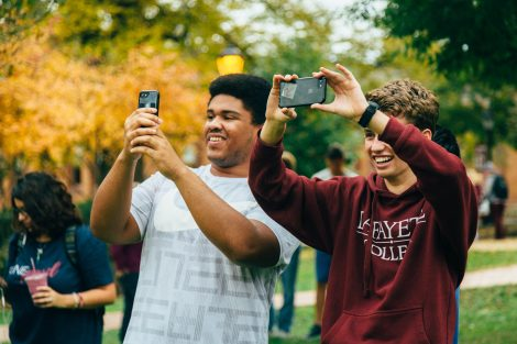 Students take photos on their phones of the hot air balloon above the Quad.