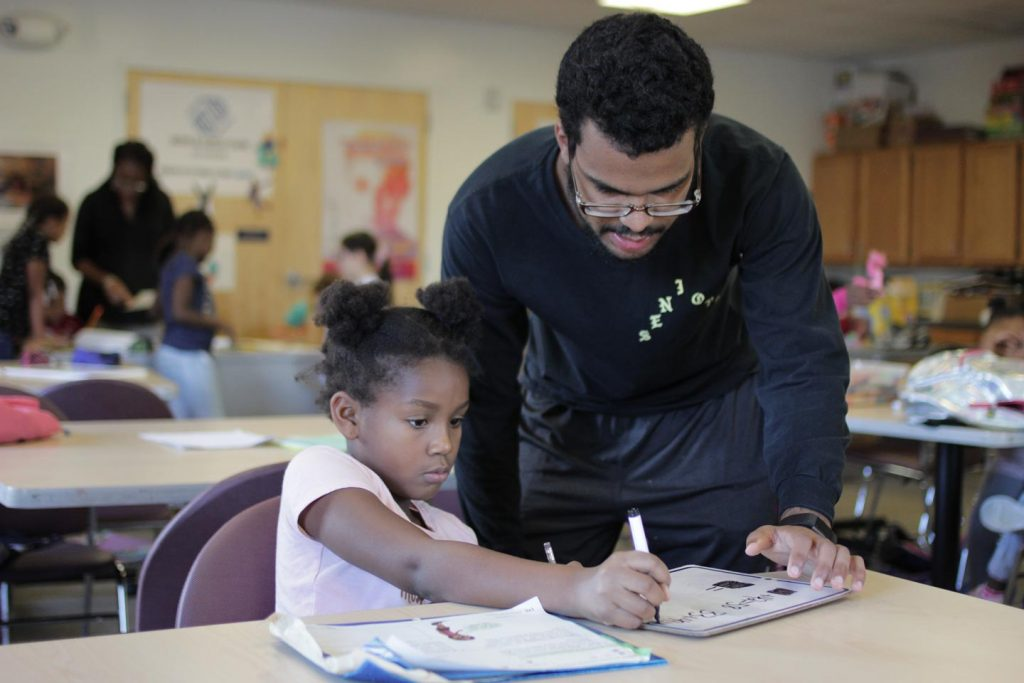 A man watches a girl use her magic marker and provides guidance at Boys and Girls Club of Easton.