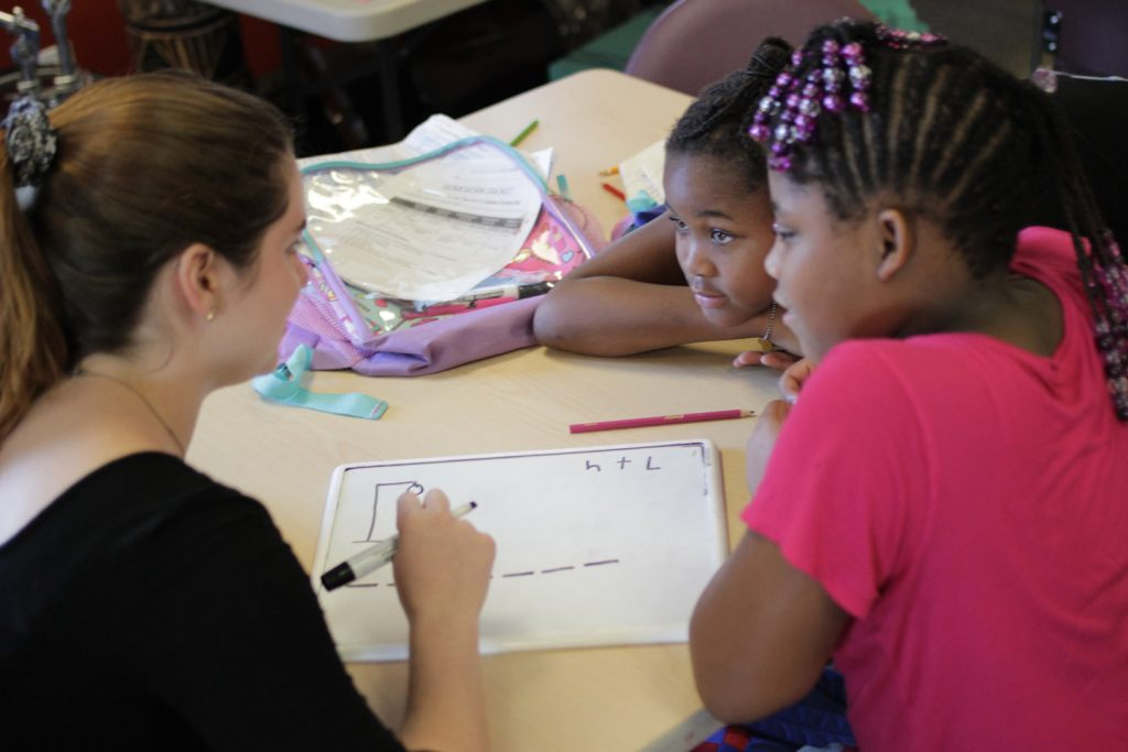 A Lafayette student holding a magic marker talks to two girls at Boys and Girls Club of Easton.