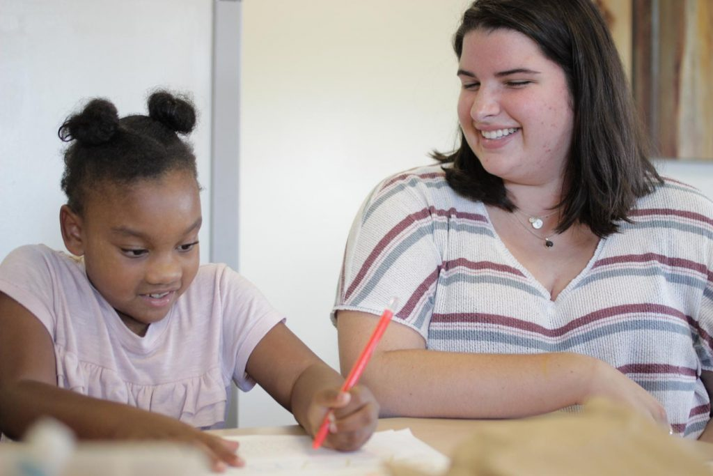 A Lafayetet student smiles while watching a girl write at Boys and Girls Club of Easton.