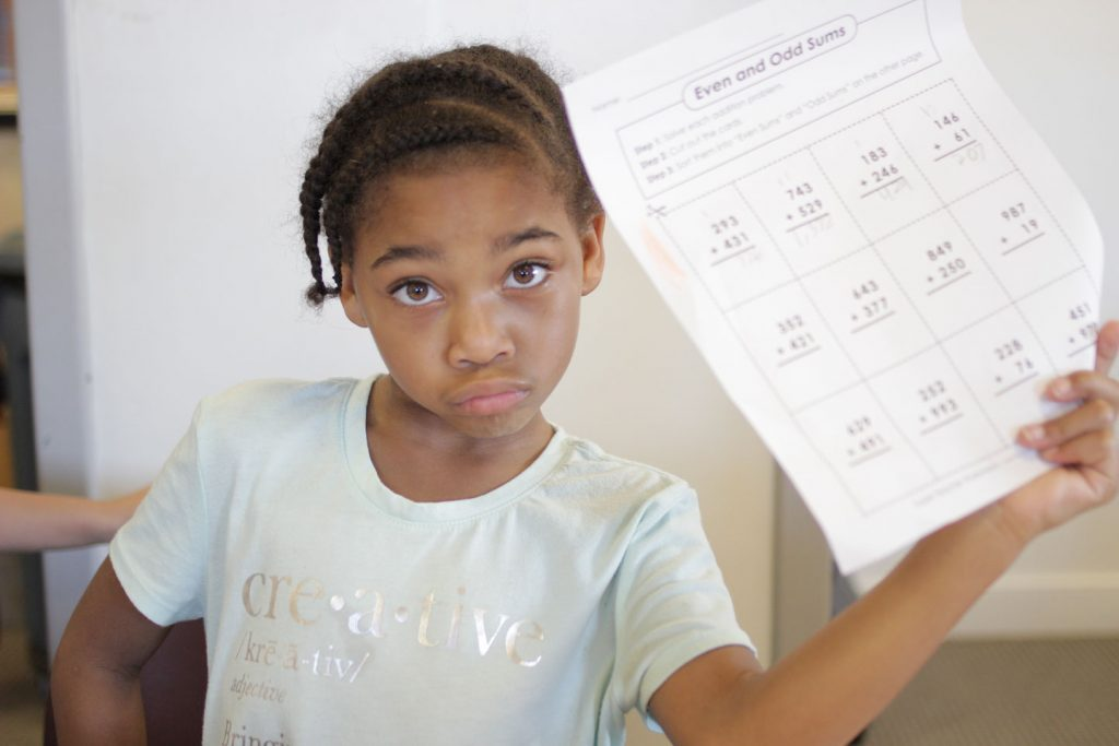A young girl holds up her math paper for the camera at Boys and Girls Club of Easton.