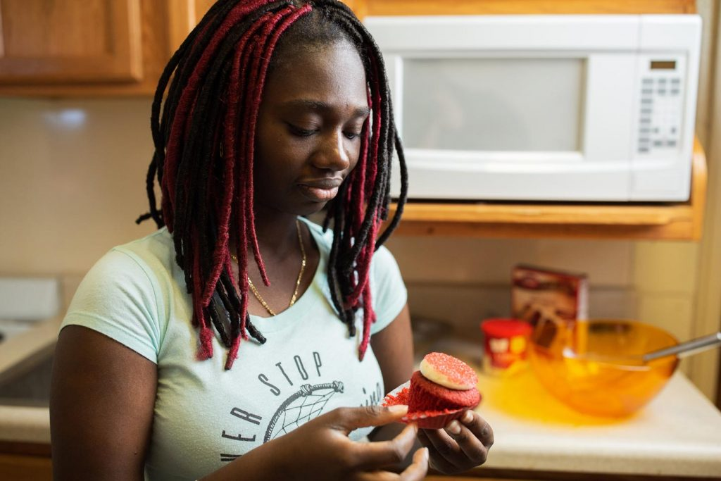 Dapha Fertil '22 removes the paper from one of her cupcakes in her dorm kitchen.