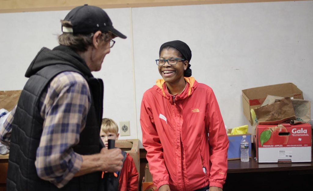 Ryana Jones '20 and a man laugh together at the St. Vincent De Paul food bank.