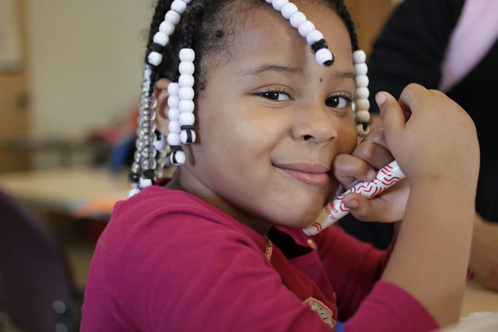 A girl smiles and holds a magic marker at Boys and Girls Club of Easton.
