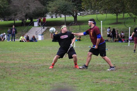 A Lafayette Quidditch player holds the ball while being defended.