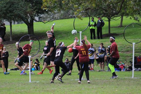 Quidditch players try to throw a ball through a hoop.