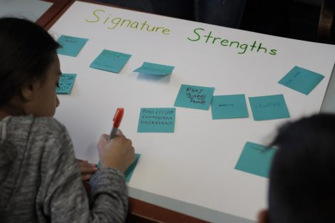 A student writes on a Post-It note