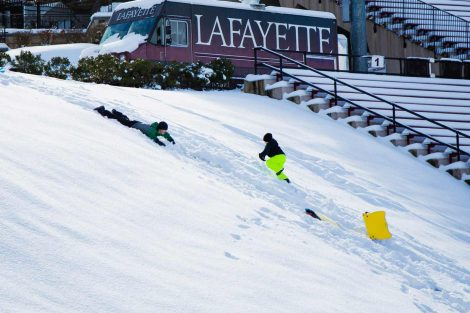 Students sled by the stands at Fisher Stadium.