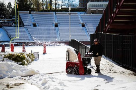 A man uses a snowblower to remove snow at Fisher Stadium.