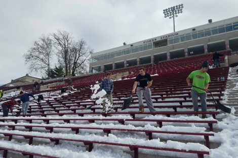 Students shovel snow from the stands at Fisher Stadium.